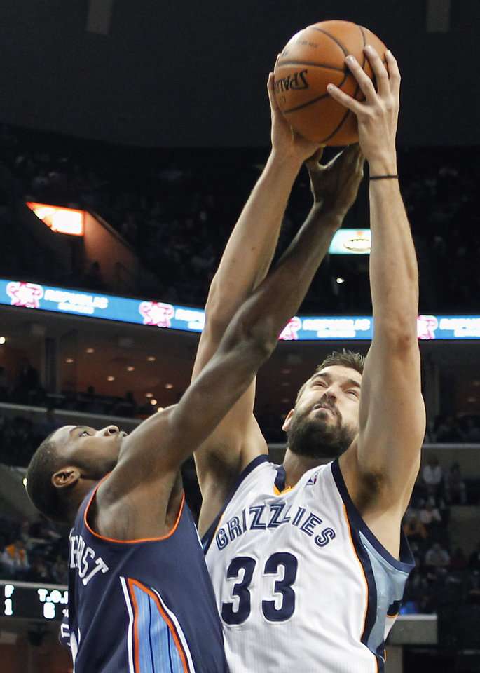 Photo - Memphis Grizzlies center Marc Gasol (33), of Spain, fights for a rebound against Charlotte Bobcats forward Michael Kidd-Gilchrist (14) in the first half of an NBA basketball game Saturday, March 8, 2014, in Memphis, Tenn. (AP Photo/Lance Murphey)