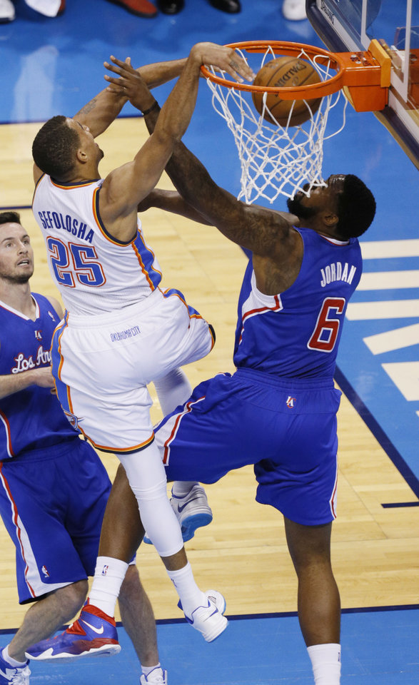 Photo - Thabo Sefolosha (25) dunks against DeAndre Jordan (6) during Game 5 of the Western Conference semifinals in the NBA playoffs between the Oklahoma City Thunder and the Los Angeles Clippers at Chesapeake Energy Arena in Oklahoma City,  Tuesday, May 13, 2014. Photo by Bryan Terry, The Oklahoman