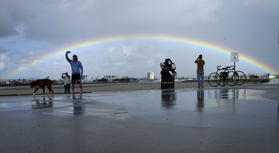 Photo - People take pictures of themselves in front of a rainbow, Tuesday, Nov. 3, 2015, in San Diego. Light rain fell on parts of San Diego county Tuesday, amid scattered rays of sunshine, providing the county with occasional rainbows. (AP Photo/Gregory Bull)