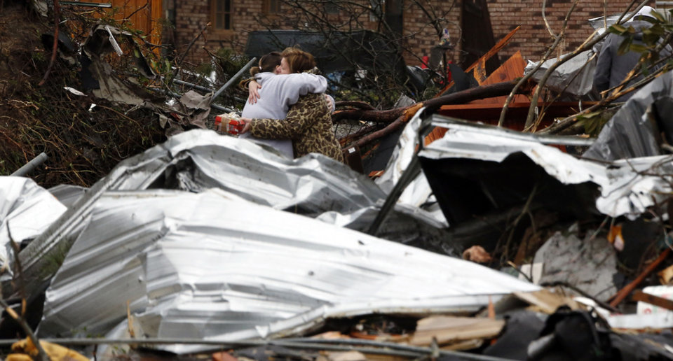 Photo - Neighbors hug amid the tornado damage in Petal, Miss., Tuesday, Feb. 12, 2013, as cleanup continues following the Sunday afternoon tornado that caused damage throughout the community. (AP Photo/Rogelio V. Solis)