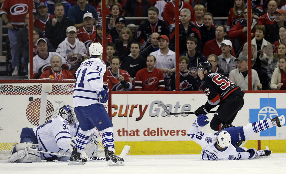 Photo - Carolina Hurricanes' Jeff Skinner (53) scores on Toronto Maple Leafs goalie James Reimer as Maple Leafs' Jay McClement (11) and Jerry D'Amigo (29) defend during the first period of an NHL hockey game in Raleigh, N.C., Thursday, Jan. 9, 2014. (AP Photo/Gerry Broome)