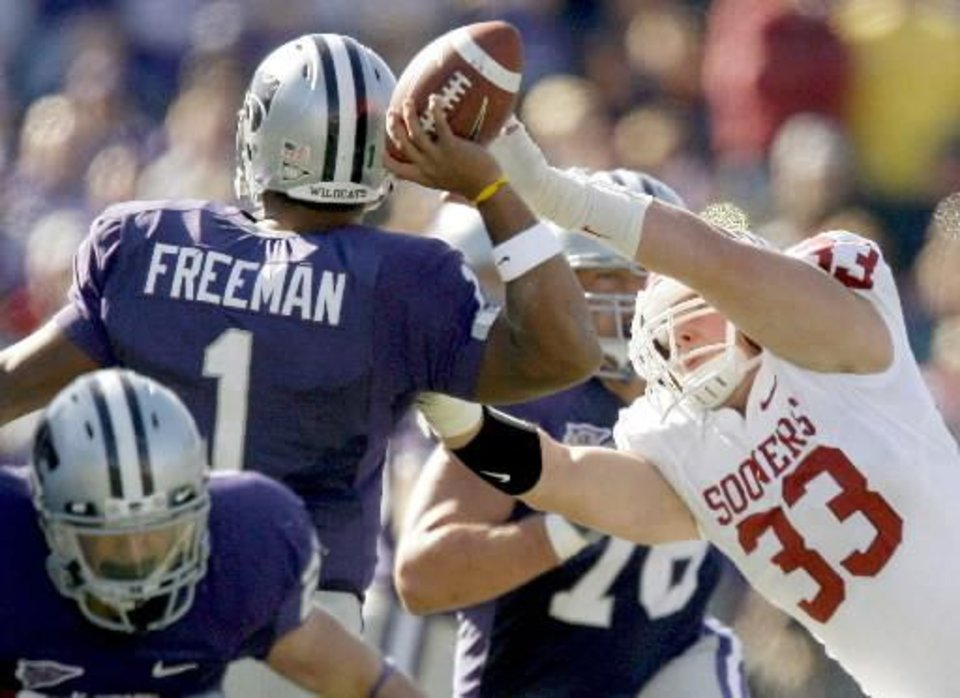 Photo - OU's  Auston  English gets a hand on the ball as Kansas State's Josh Freeman throws an interception during last Saturday's game. By Bryan Terry.