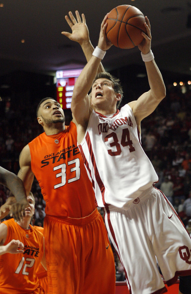 Photo - OU's Cade Davis (34) drives to the basket past OSU's Marshall Moses (33) during the second half of the college bedlam basketball game between The University of Oklahoma Sooners (OU) and Oklahoma State University University Cowboys (OSU) at the Lloyd Noble Center on Monday, Jan. 11, 2010, in Norman, Okla.