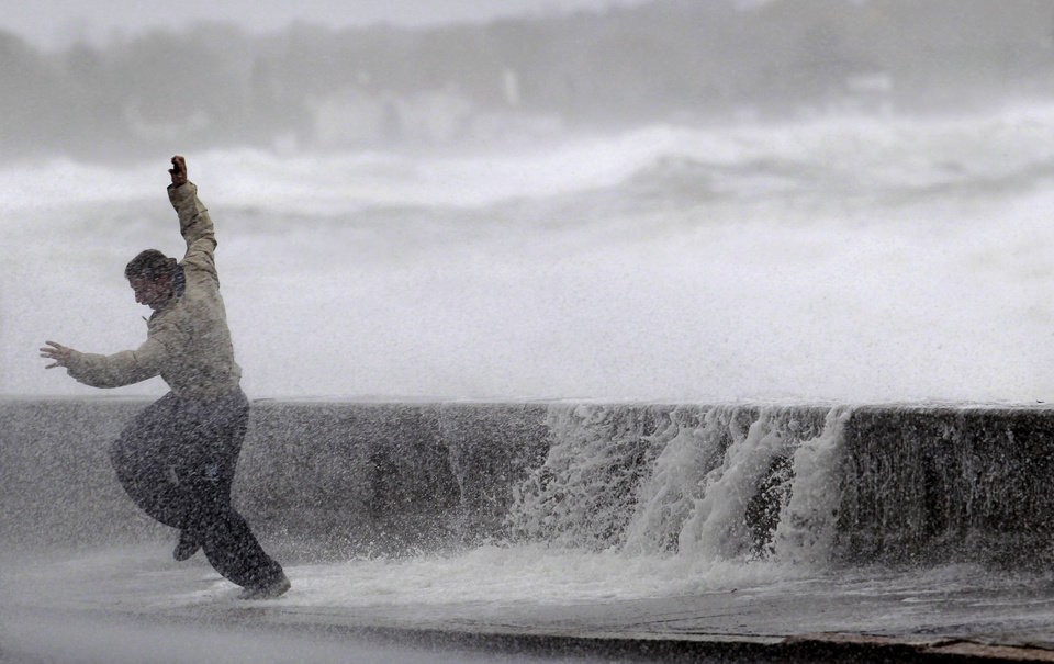 Photo -   A man reacts to waves crashing over a seawall in Narragansett, R.I., Monday, Oct. 29, 2012. A fast-strengthening Hurricane Sandy churned north Monday, raking ghost-town cities along the Northeast corridor with rain and wind gusts. (AP Photo/Steven Senne)