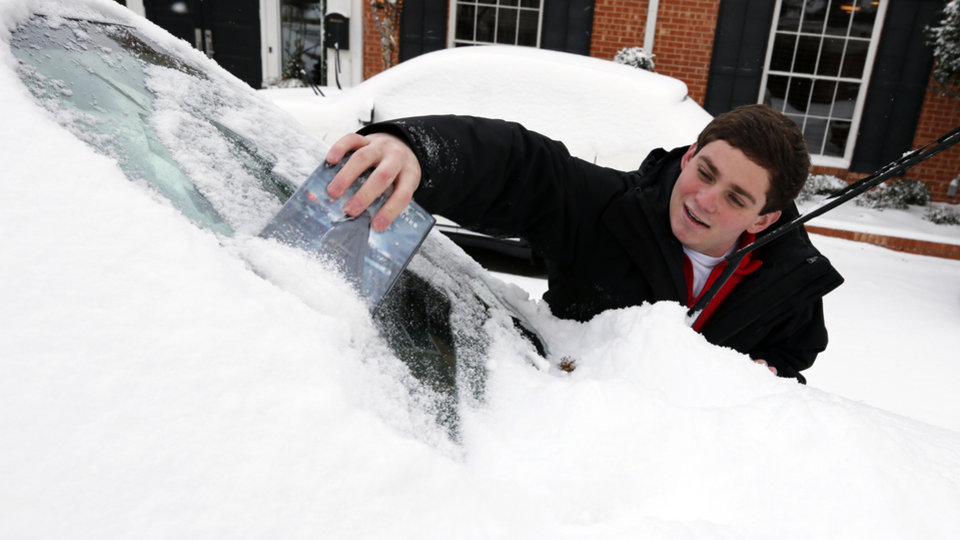 Hunter Burkhalter, OU junior from Plano, Texas, uses a video case to remove snow from his windshield at the University of Oklahoma (OU) on Friday, Dec. 6, 2013 in Norman, Okla. Photo by Steve Sisney, The Oklahoman