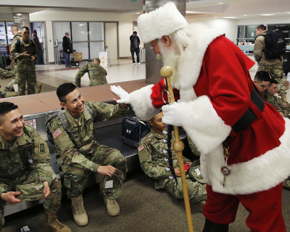 Photo - Santa Claus gives a high-five to Private William Ortiz, from California, as soldiers from Ft. Sill gather at Will Rogers World Airport in Oklahoma City, Okla. on their way home for Christmas, Monday, Dec. 19, 2016.  Photo by Paul Hellstern, The Oklahoman