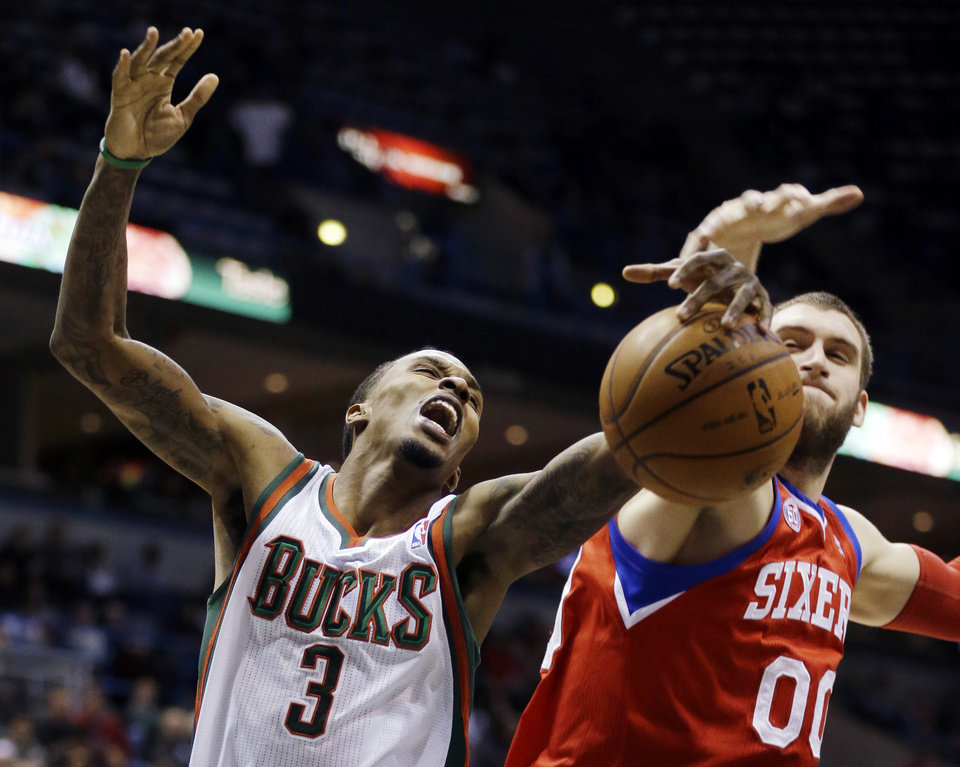 Milwaukee Bucks' Brandon Jennings (3) and Philadelphia 76ers' Spencer Hawes (00) reach for a rebound during the second half of an NBA basketball game, Tuesday, Jan. 22, 2013, in Milwaukee. The Bucks won 110-102. (AP Photo/Jeffrey Phelps)