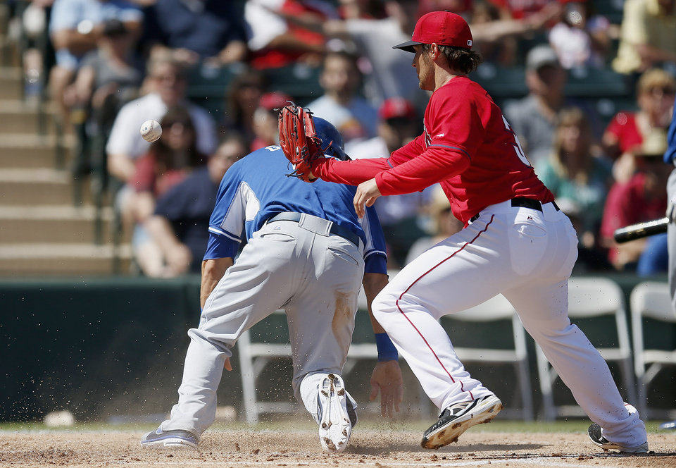 Photo - Kansas City Royals' Alex Gordon, left, scores a run as Los Angeles Angels' C.J. Wilson is unable to catch the ball during the first inning of a spring training baseball game Friday, March 21, 2014, in Tempe, Ariz. (AP Photo/Ross D. Franklin)