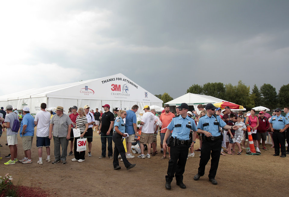 Photo - Security personnel manage the crowd after a weather delay was issued during the second round of the Champions Tour's 3M Championship golf tournament at TPC Twin Cities in Blaine, Minn., Saturday, Aug. 2, 2014. AP Photo/Paul Battaglia)