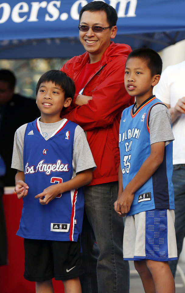 Photo - Brothers Matthew Jutabha, 9, and Ben Jutabha, 10, of Los Angeles, wear competing jerseys as they stand with their father, Charlie Jutabha outside the arena before Game 3 of the Western Conference semifinals in the NBA playoffs between the Oklahoma City Thunder and the Los Angeles Clippers at the Staples Center in Los Angeles, Friday, May 9, 2014. Photo by Nate Billings, The Oklahoman