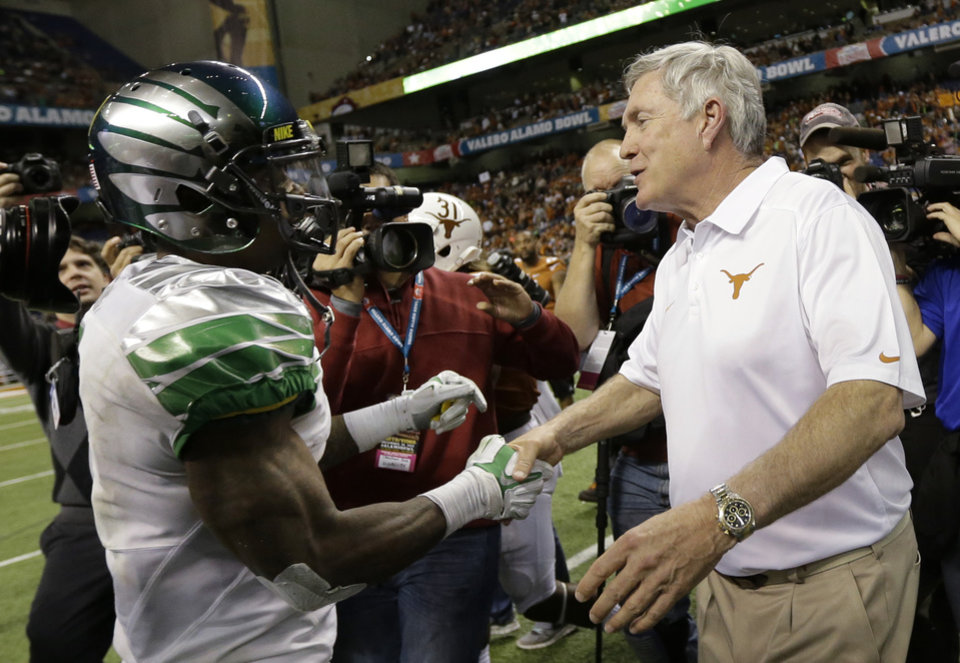 Photo - Texas coach Mack Brown, right, shakes hands with Oregon quarterback Marcus Mariota, left, after  the Valero Alamo Bowl NCAA college football game, Monday,  Dec. 30, 2013, in San Antonio. Oregon won 30-7. (AP Photo/Eric Gay)