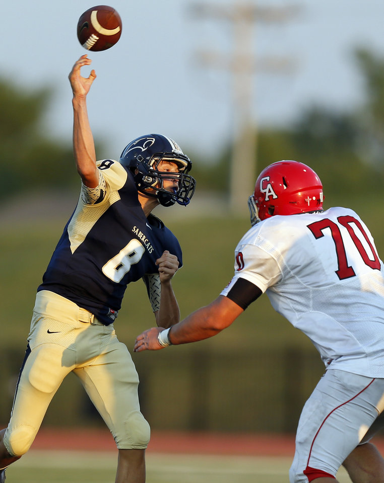 Photo - Southmoore's Conner Uselton (8) passes as he is pressured by Tyler Banta (70) of Carl Albert during a high school football game between Southmoore and Carl Albert at Moore Schools Stadium in Moore, Okla., Thursday, Sept. 5, 2013.  Photo by Nate Billings, The Oklahoman
