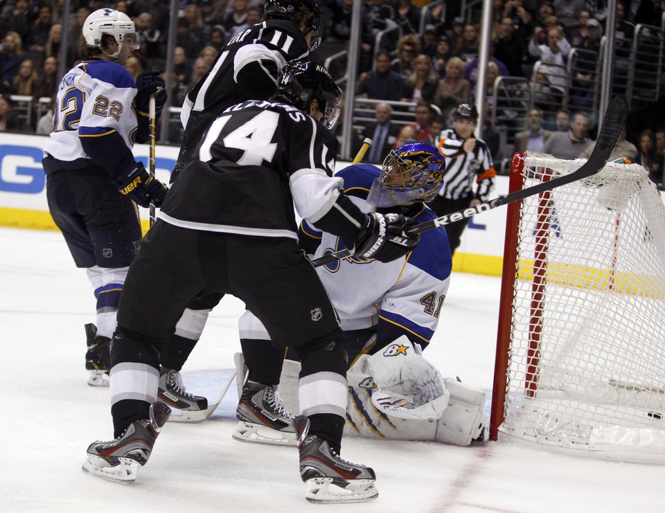 Photo - The puck gets by St. Louis Blues goalie Jaroslav Halak, right, of the Czech Republic with Los Angeles Kings center Anze Kopitar (11), of Yugoslavia, and Kings right wing Justin Williams (14) attacking for a goal during the second period of an NHL hockey game Tuesday, March 5, 2013, in Los Angeles.  (AP Photo/Alex Gallardo)