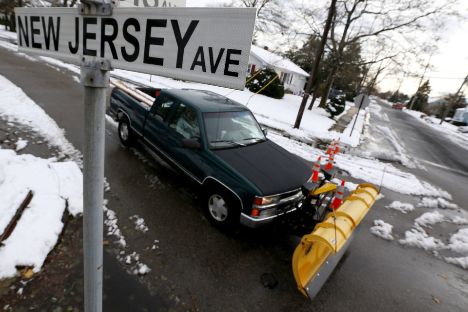 Photo - A snow plower drives on New Jersey Avenue as snow covered debris from  Superstorm Sandy lies on the sidewalk, Thursday, Nov. 8, 2012, in Point Pleasant, N.J.  A nor'easter hit the New Jersey shore on Wednesday, pounding the region which was already hit by Superstorm Sandy. (AP Photo/Julio Cortez) ORG XMIT: NJJC122