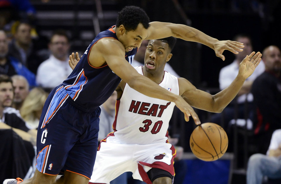 Photo - Charlotte Bobcats' Gerald Henderson, left, drives past Miami Heat's Norris Cole (30) during the second half of their NBA basketball game, Wednesday, Dec. 26, 2012, in Charlotte. The Heat won 105-92. (AP Photo/The Charlotte Observer, David T. Foster III) MAGS OUT; TV OUT; NEWSPAPER INTERNET ONLY
