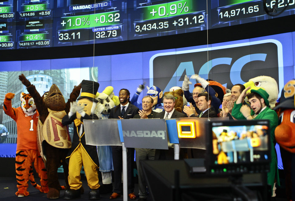 Photo - Atlantic Coast Conference mascots join ACC and NASDAQ officials for the ringing of the closing bell on Monday, July 1, 2013 in New York.  The Atlantic Coast Conference officials and coaches visited the NASDAQ Market Site in Times Square to officially announce the addition of its three new members in Notre Dame, Pitt and Syracuse. (AP Photo/Bethan McKernan)