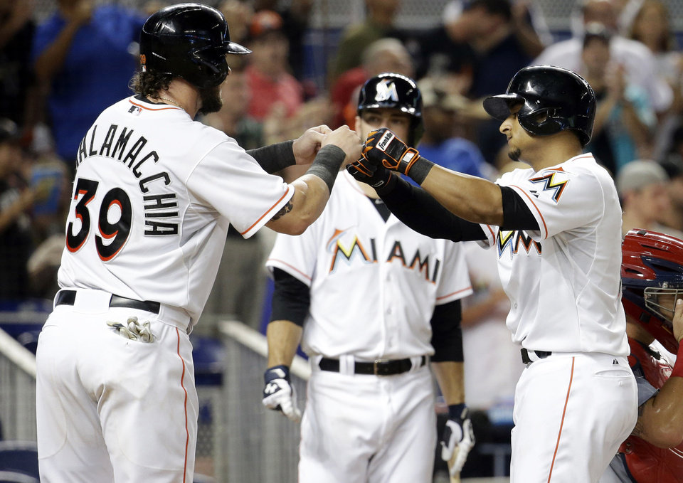 Photo - Miami Marlins' Donovan Solano, right, is met at the plate by Jarrod Saltalamacchia, left, after they scored on a two-run home run hit by Solano in the fourth inning during a baseball game against the St. Louis Cardinals, Tuesday, Aug. 12, 2014, in Miami. (AP Photo/Lynne Sladky)