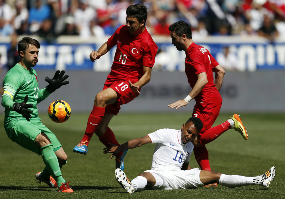 Photo - United States' Julian Green (16) goes down while trying to score on Turkey goalkeeper Onur Recep Kivrak, left, in the second half of an international soccer friendly, Sunday, June 1, 2014, in Harrison, N.J. Also defending are Ozan Tufan, center, and Gokhan Gonul. The U.S. won 2-1. (AP Photo/Julio Cortez)