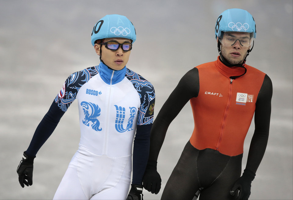Photo - Victor An of Russia, left, and Sjinkie Knegt of Netherlands leave the ice after competing in a men's 1000m short track speedskating quarterfinal at the Iceberg Skating Palace during the 2014 Winter Olympics, Saturday, Feb. 15, 2014, in Sochi, Russia. (AP Photo/Ivan Sekretarev)