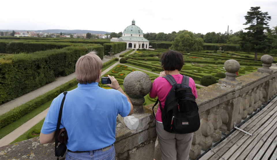 Photo - In this Aug. 7, 2014, photo, tourists take photos of UNESCO's Flower Garden in city of Kromeriz, Czech Republic.  A visit to the Flower Garden is like traveling 300 years back in time. With its original geometrical layout and high topiary walls, it's a rare example of an early Baroque garden style. (AP Photo/Petr David Josek)