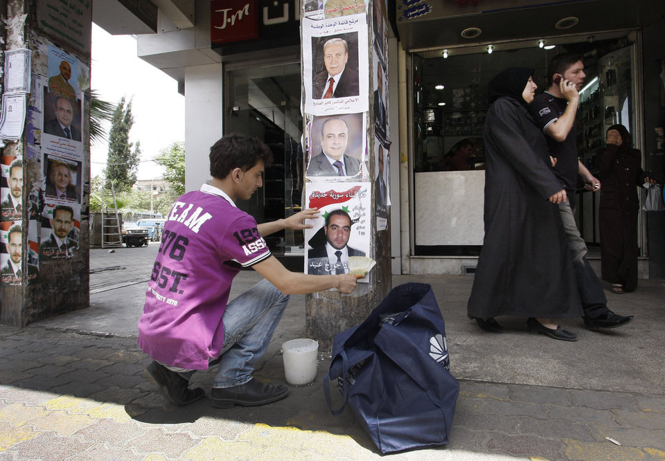 Photo -   A Syrian worker places a poster of a paramilitary candidate for the upcoming elections, in Damascus, Syria, Wednesday, May 2, 2012. Preparations are underway in Syria for the parliamentary elections slated for May 7, 2012, as the crisis in the country drags on. (AP Photo/Muzaffar Salman)