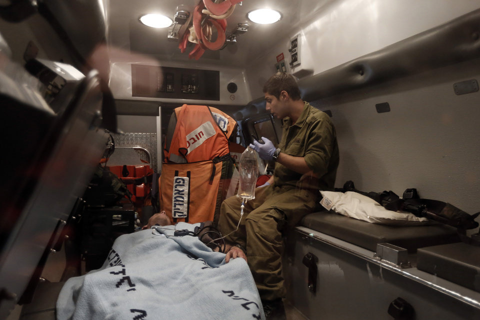Photo -   A wounded Israeli soldier is evacuated by ambulance on the Israel-Gaza border in southern Israel, Saturday, Nov. 10, 2012. An explosion targeted an Israeli military vehicle on the Jewish state's border with Gaza on Saturday and Israeli troops fired into the Palestinian territory killing several civilians and wounding at least 25, Gaza officials and witnesses said. (AP Photo / Tsafrir Abayov)