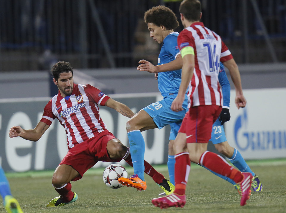 Photo - Atletico's Raul Garcia, left, and Zenit's Axel Witsel struggle for the ball during the Champions League group G soccer match between Zenit and Atletico Madrid at Petrovsky stadium in St.Petersburg, Russia, on Wednesday, Nov. 27, 2013. (AP Photo/Dmitry Lovetsky)