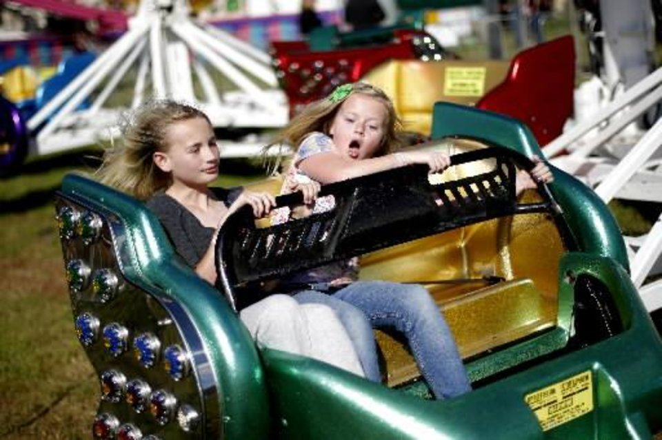 Katie Pollard , 11, left, Emma Chesnut, 10, react as they hold on during a ride at the Guthrie 89er Day Celebration, Friday, April 20, 2012. Photo by Bryan Terry, The Oklahoman Archives