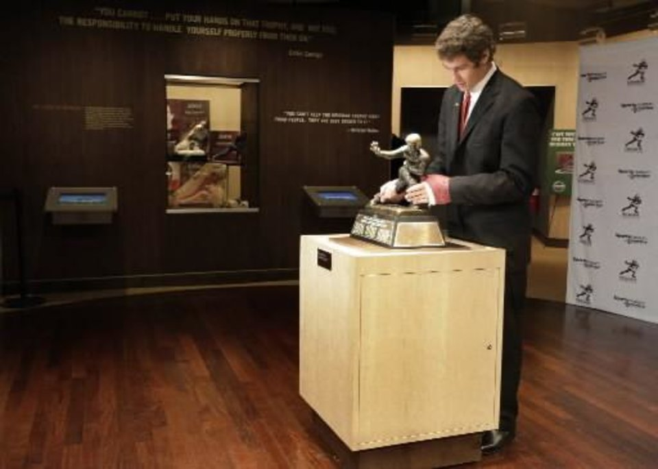 Photo - Oklahoma football player  Sam  Bradford puts his hands on the original Heisman Trophy, which is on display at the Sports Museum of America, after being awarded the Heisman Trophy Saturday, Dec. 13, 2008 in New York. (AP Photo/Julie Jacobson)