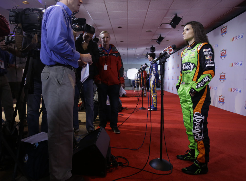 Driver Danica Patrick, right,  answers questions during  NASCAR auto racing media day at Daytona International Speedway in Daytona Beach, Fla., Thursday, Feb. 13, 2014. (AP Photo/John Raoux)