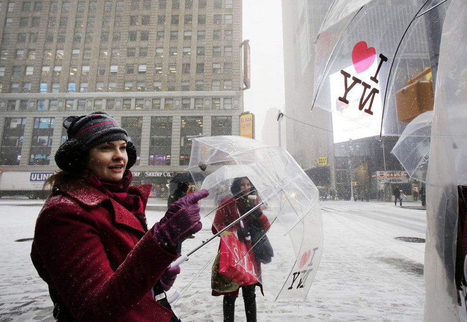 Photo - Vanessa Niels, of Santa Catarina, Brazil, buys an umbrella from a vendor during a snowfall, Tuesday, Jan. 21, 2014 in New York's Times Square. A storm is sweeping across the mid Atlantic states and New England.  The National Weather Service said the storm could bring 8 to 12 inches of snow to Philadelphia and New York City, and more than a foot in Boston. Bitterly cold air with wind chills as low as 10 degrees below zero was forecast. (AP Photo/Mark Lennihan)