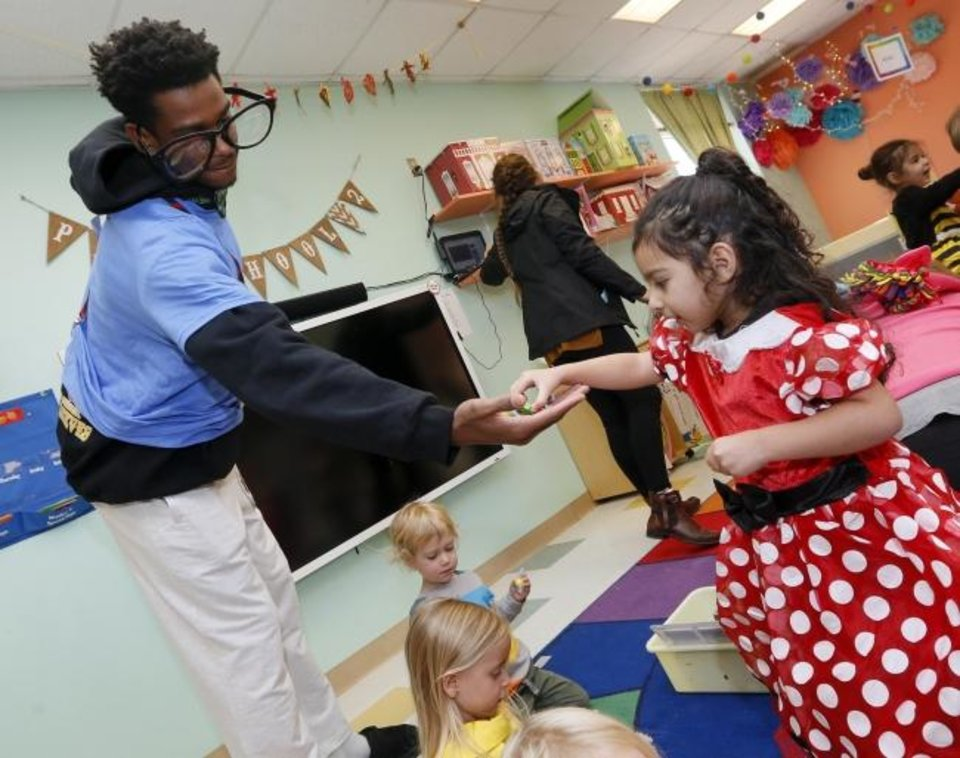 Photo -  Oklahoma City's Shai Gilgeous-Alexander gives candy to Aaliyah Alhassawy, 3, on Thursday at Special Care. [Nate Billings/The Oklahoman]