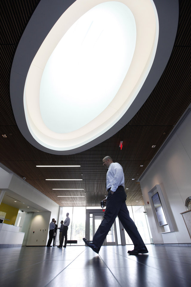 In this Monday, Nov. 12, 2012, photo, a worker walks under the skylight in the lobby of the Commonwealth Center for Advanced Manufacturing, in Prince George, Va. The Commonwealth Center for Advanced Manufacturing is conducting research for a group of manufacturing companies under a partnership with Virginia Tech, Virginia State University and the University of Virginia. (AP Photo/Steve Helber)