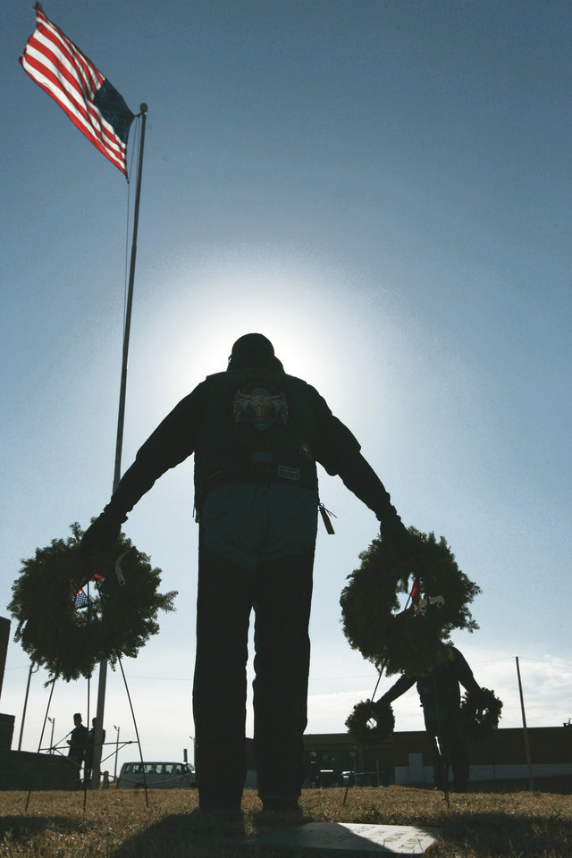 Photo - Mark Johns holds wreaths at Oklahoma Veterans Cemetery during a Wreaths Across America ceremony on Saturday. Johns is a member of the Iron Plainsmen Motorcycle Club, a brotherhood of law enforcement oficers, their spouses, and friends.  Photo by Steve Gooch, the oklahoman