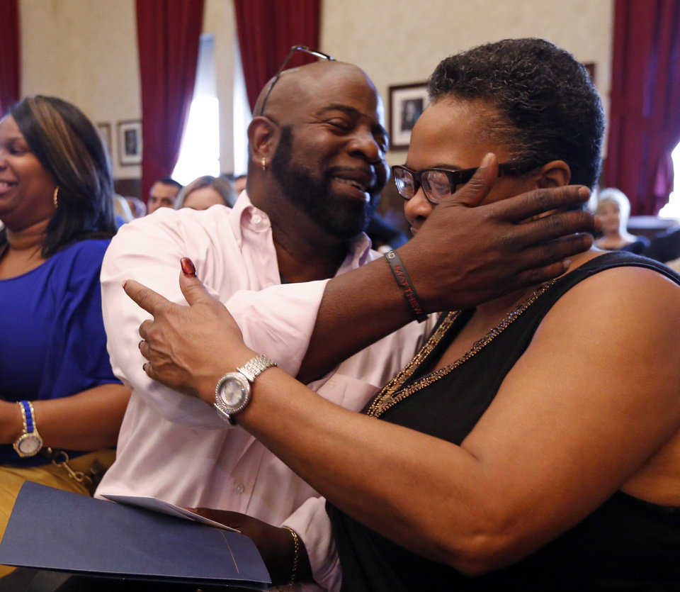 Photo -  Al Anderson hugs his sister, A. Cooper, after his graduation Thursday from drug court in the Cleveland County Courthouse. [Photo by Steve Sisney, The Oklahoman]