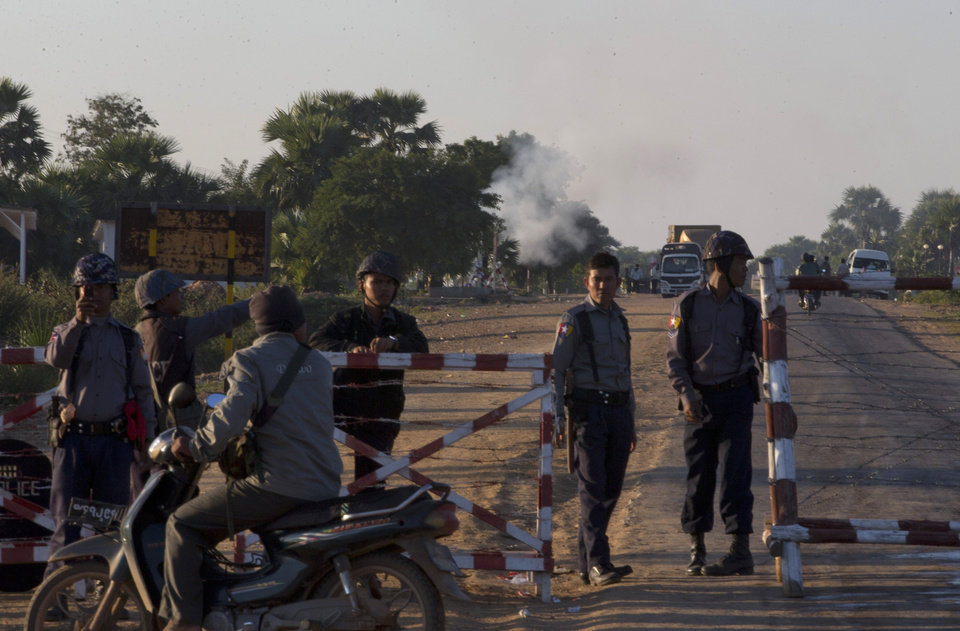 Photo - Myanmar police officers stand guard at the entry point to Letpadaung mine in Monywa, northwestern Myanmar, Thursday, Nov 29, 2012.    Security forces cracked down on protesters occupying a copper mine early Thursday, using water cannons and other devices to break up the rally hours before opposition leader Aung San Suu Kyi was expected to hear their grievances. Unexplained fires engulfed the protest camps at the Letpadaung mine in northwestern Myanmar and dozens of Buddhist monks and villagers were injured. (AP Photo/Gemunu Amarasinghe)