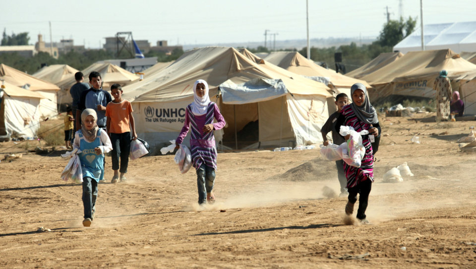 Photo -   Syrian refugee children run while carrying traditional gifts of toys and clothes they received from individual donors and international organizations on the first day the Muslim holiday of Eid al- Fitr at the Zaatari Refugee Camp in Mafraq, Jordan, Sunday, Aug. 19, 2012. Muslims around the world celebrate Eid al-Fitr, marking the end of Ramadan, the Muslim calendar's ninth and holiest month during which followers are required to abstain from food and drink from dawn to dusk. (AP Photo/Mohammad Hannon)