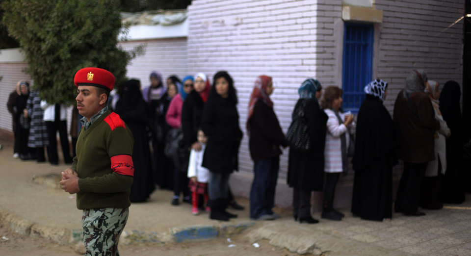 Photo - An Egyptian soldier stands guard outside a polling site during a referendum on a disputed constitution drafted by Islamist supporters of President Mohammed Morsi in Cairo, Egypt, Saturday, Dec. 15, 2012. Egyptians were voting on Saturday on a proposed constitution that has polarized their nation, with Morsi and his Islamist supporters backing the charter, while liberals, moderate Muslims and Christians oppose it. (AP Photo/Khalil Hamra)