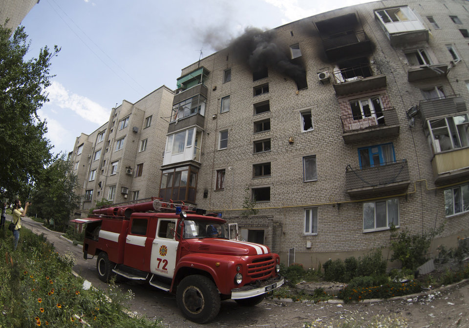 Photo - A fire truck arrives at a burning building after shelling in Maryinka village, outside the city of Donetsk, eastern Ukraine, Saturday, July 12, 2014. (AP Photo/Dmitry Lovetsky)