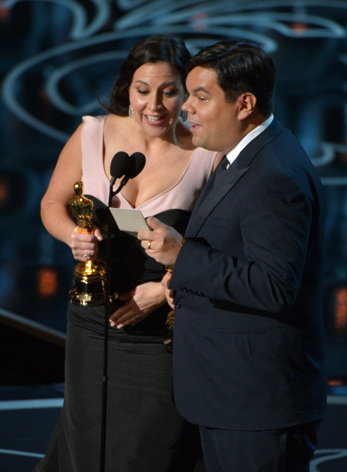 Photo - Kristen Anderson-Lopez, left, and Robert Lopez accept the award for an original song in a feature film for