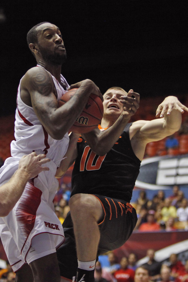 NC State's Richard Howell, left, battle for a rebound against Oklahoma State's Phil Forte during a NCAA college basketball game in Bayamon, Puerto Rico, Sunday, Nov. 18, 2012. (AP Photo/Ricardo Arduengo)