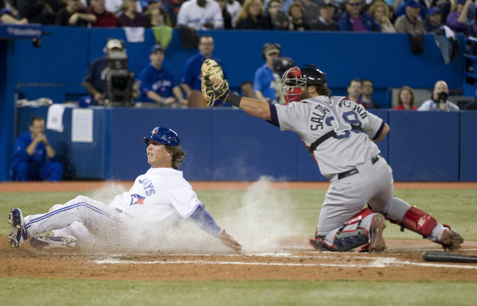 Photo -   Toronto Blue Jays' Colby Rasmus scores past Boston Red Sox catcher Jarrod Saltalamacchia on a grounder by Kelly Johnson during the third inning of a baseball game in Toronto on Monday, April 9, 2012. (AP Photo/The Canadian Press, Frank Gunn)