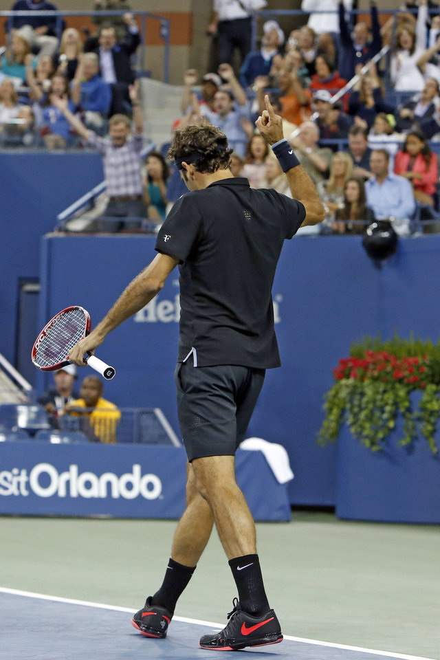 Photo - The crowd cheers as Roger Federer, of Switzerland, reacts after winning a point against Sam Groth, of Australia, during the second round of the U.S. Open tennis tournament Friday, Aug. 29, 2014, in New York. (AP Photo/Jason DeCrow)
