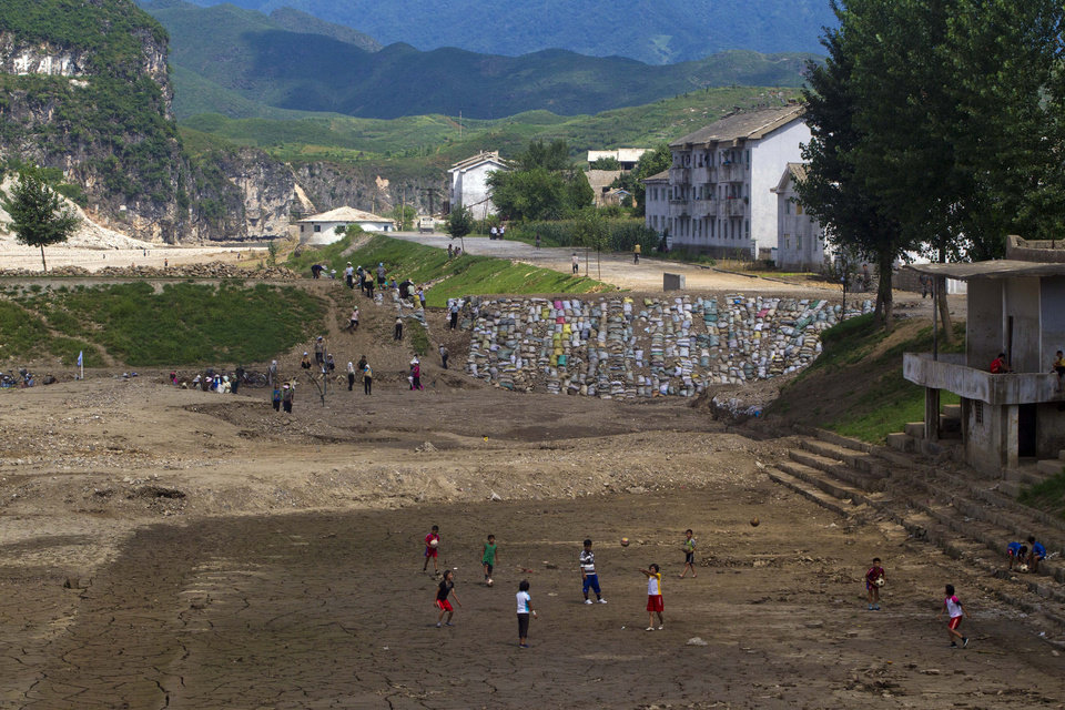 Photo -   In this Monday, Aug 13, 2012 photo, North Koreans practice volleyball in a mud covered field as others work to build a sandbag wall trying to repair damage brought by July flooding in Songchon County, North Korea. Twin typhoons are renewing fears of a humanitarian crisis in North Korea, where poor drainage, widespread deforestation and fragile infrastructure can turn even a routine rainstorm into a catastrophic flood. (AP Photo/David Guttenfelder)