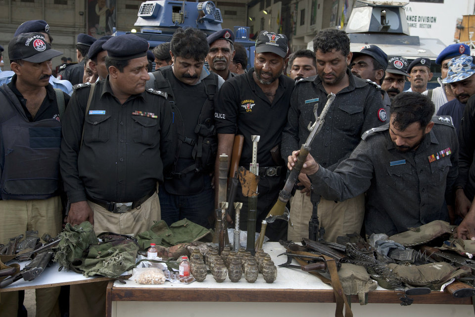 Photo - Pakistani police officers display ammunition confiscated from attackers at the Jinnah International Airport, Monday, June 9, 2014, in Karachi, Pakistan. Gunmen disguised as police guards attacked a terminal at Pakistan's busiest airport with machine guns and a rocket launcher during a five-hour siege that killed over a dozen people as explosions echoed into the night, while security forces retaliated and killed all the attackers, officials said Monday.  (AP Photo/Shakil Adil)