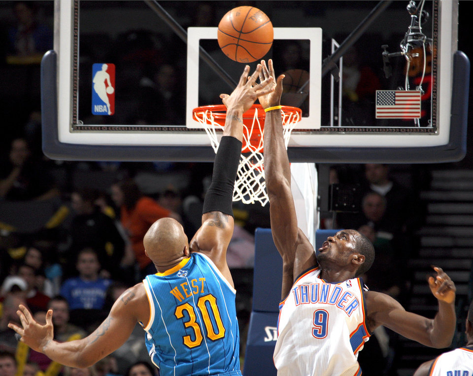 Photo - Oklahoma City's Serge Ibaka (9) blocks New Orleans' David West (30) shot during the NBA basketball game between Oklahoma City Thunder and New Orleans Hornet, Wednesday, Feb. 2, 2011 at the Oklahoma City Arena. Photo by Sarah Phipps, The Oklahoman