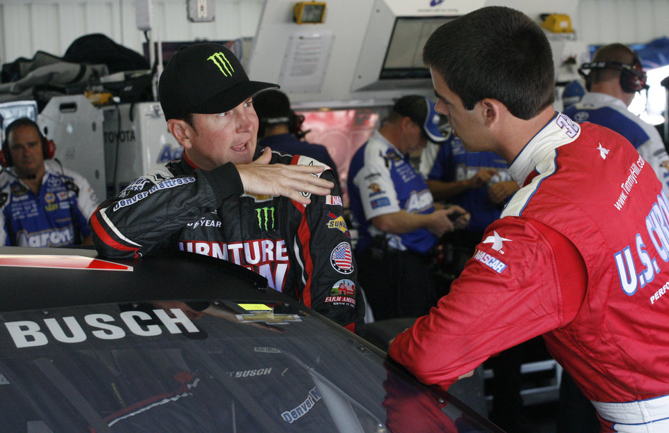 Photo - Drivers Kurt Busch, left, and Timmy Hill talk in the garage during practice for Sunday's NASCAR Sprint Cup Series auto race, Friday Aug. 2, 2013, in Long Pond, Pa. (AP Photo/Russ Hamilton Jr.)