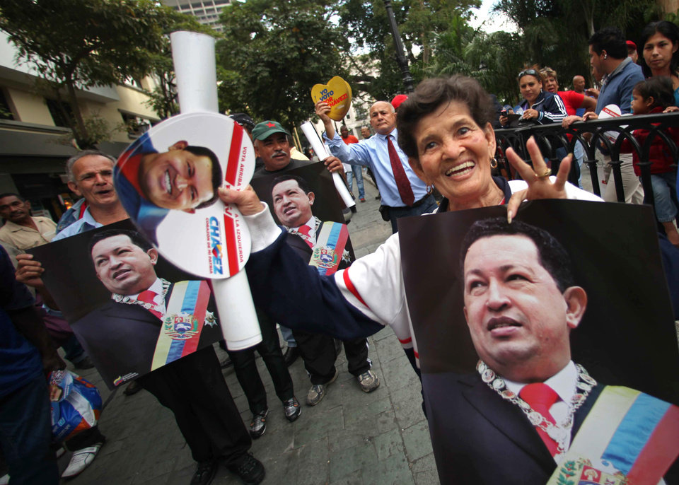 A woman reacts to the camera as supporters holding pictures gather in Bolivar square after President Hugo Chavez\' return in Caracas, Venezuela, Monday, Feb. 18, 2013. Chavez returned to Venezuela early Monday after more than two months of medical treatment in Cuba following cancer surgery. The government didn\'t offer an explanation as to why Chavez made his surprise return while he is undergoing other treatments that have not been specified.(AP Photo/Fernando Llano)