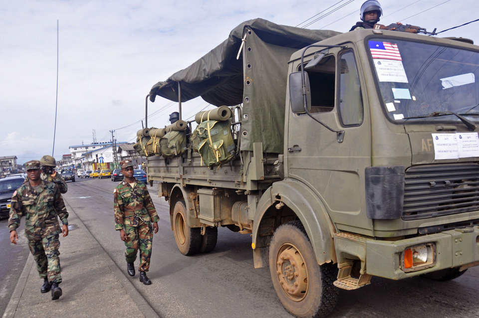 Photo - Liberian soldiers walk through streets to prevent panic as fears of the deadly Ebola virus spread in the city of Monrovia, Liberia, Friday, Aug. 1, 2014. U.S. health officials warned Americans not to travel to the three West African countries hit by the worst recorded Ebola outbreak in history. The travel advisory issued Thursday applies to nonessential travel to Guinea, Liberia and Sierra Leone, where the deadly disease has killed more than 700 people this year. (AP Photo/Abbas Dulleh)