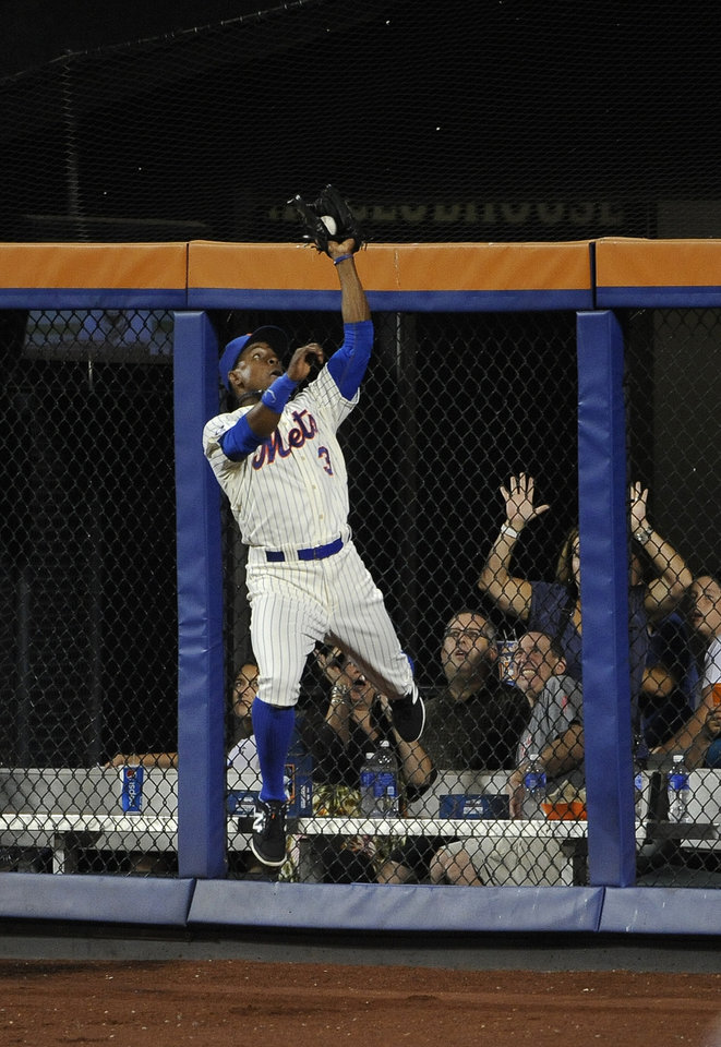 Photo - New York Mets right fielder Curtis Granderson leaps against the outfield wall to catch Philadelphia Phillies' Jimmy Rollins fly ball in the fourth inning of a baseball game at Citi Field on Saturday, Aug. 30, 2014, in New York. (AP Photo/Kathy Kmonicek)